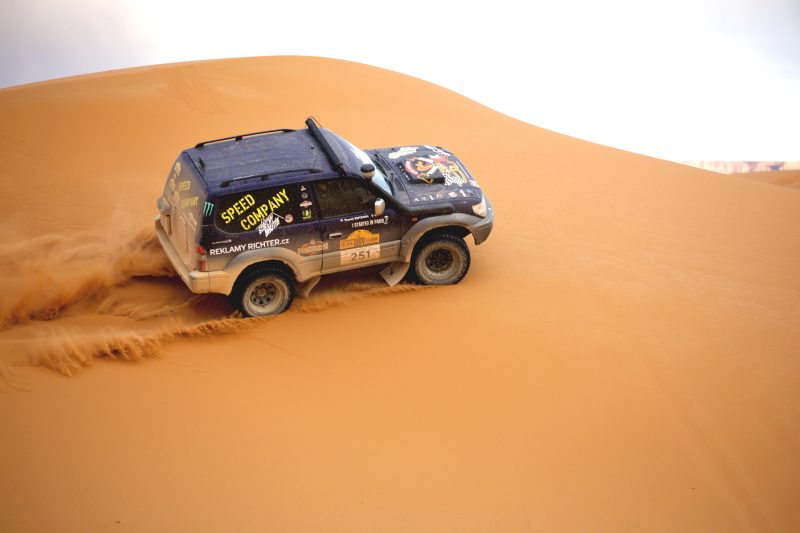 Rally car in sand dunes real way to dakar